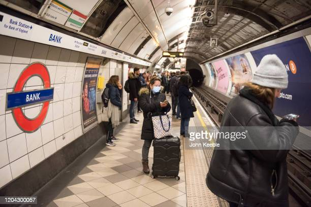 A woman wears a face mask while waiting for a tube train at Bank underground station on March 01 2020 in London England There has been three more...