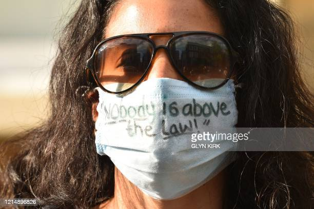 A woman wears a face mask with a message written on it that reads nobody is above the law outside the home of Number 10 Downing Street special...