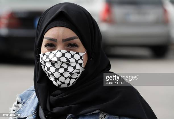 Woman wears a face mask with the patterns of the Kaffiyeh, the chequered scarf that is worn by Palestinians to symbolise struggle, made Palestinian...