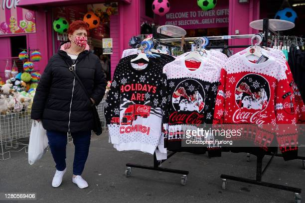 Woman wears a face masks against Covid-19 as she walks past Christmas jumpers for sale on the promenade on October 16, 2020 in Blackpool, England....