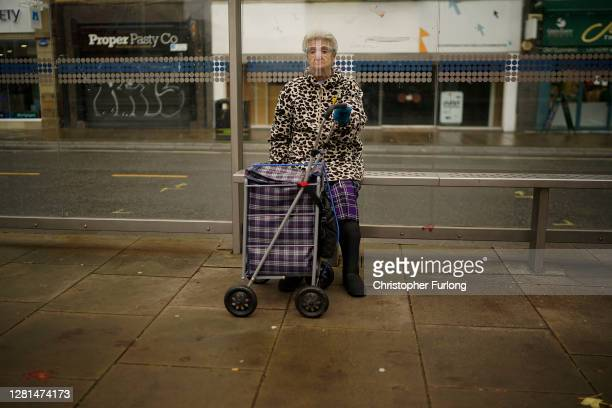 Woman wears a face shield as she sits at a bus stop on October 22, 2020 in Sheffield, England. The county of South Yorkshire, which includes the city...