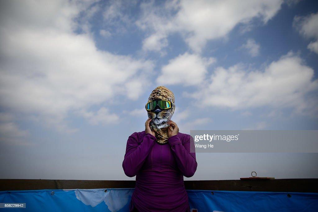 A woman wears a face-kini in Qidong Golden Beach during the 3rd Qidong YuanTuoJiao Kite Surfing Invitational Tournament on October 6, 2017 in Nantong, Jiangsu Province ,China.