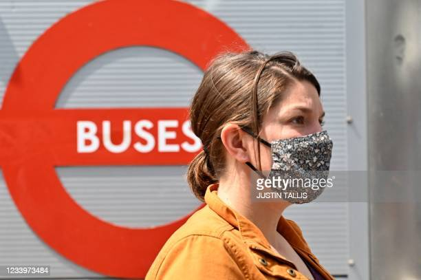 Woman wears a facemask as a preventative measure against Covid-19 as she waits at a bus stop in central London on July 14, 2021. - London Mayor Sadiq...