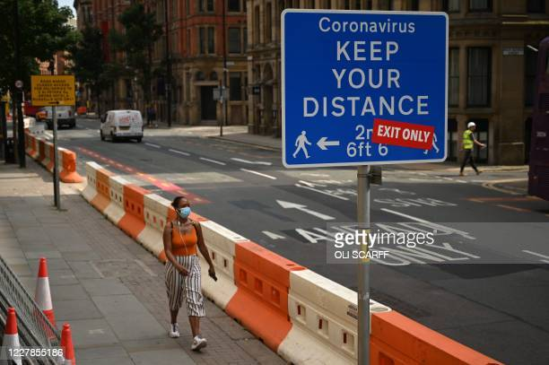 """Woman wears a facemask as she walks in the centre of Manchester, northwest England, on July 31, 2020. - Britain on Friday """"put the brakes on"""" easing..."""