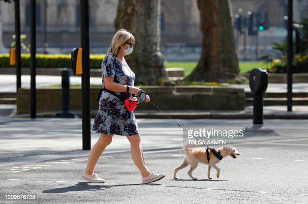 A woman wears a facemask das she walks her dog in Westminster London on April 10 2020 as warm weather tests the nationwide lockdown due to the novel...