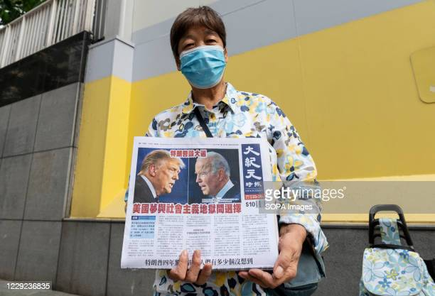 Woman wears a facemask distributes the multi-language newspaper The Epoch Times newspaper featuring the US election debate between Donald J. Trump...