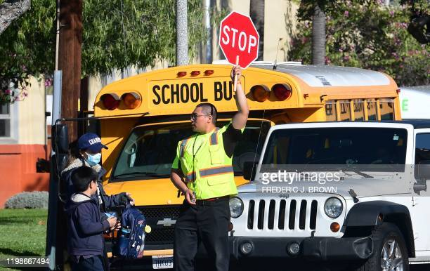 Woman wears a facemask picking up a child as an Alhambra Unified School District crossing guard stops traffic outside Ramona Elementary School on...