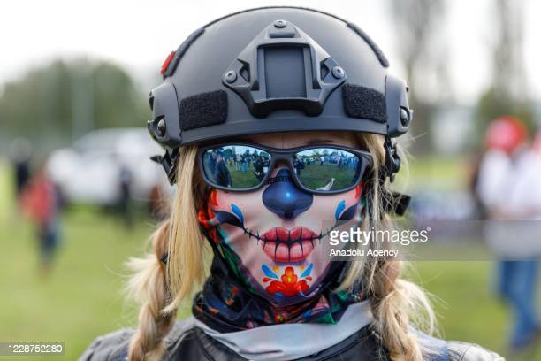 A woman wears a full face mask as the Proud Boys a rightwing proTrump group gather with their allies in a rally called âEnd Domestic Terrorismâ...