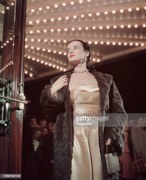 A woman wears a fur coat over an ivory strapless evening dress as she enters a theatre for a special performance in the West End of London in...