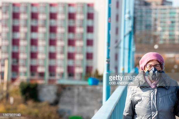 Woman wears a gas mask as she and other Poles returning home walk across the bridge over river Oder at the Polish-German border from the eastern...