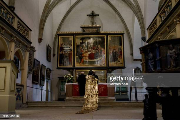 A woman wears a golden coat as a symbol of the indulgence during a service in Stadtkirche Sankt Marien to commemorate the 500th anniversary of...