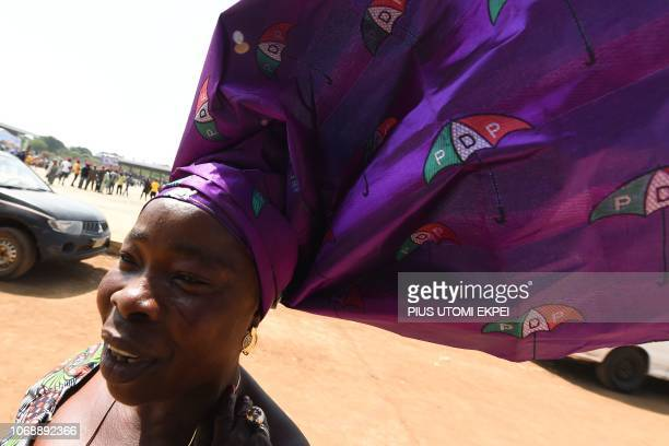 A woman wears a headdress decorated with the logo of the Nigeria's opposition party Peoples Democratic Party as she arrives for the presidential...