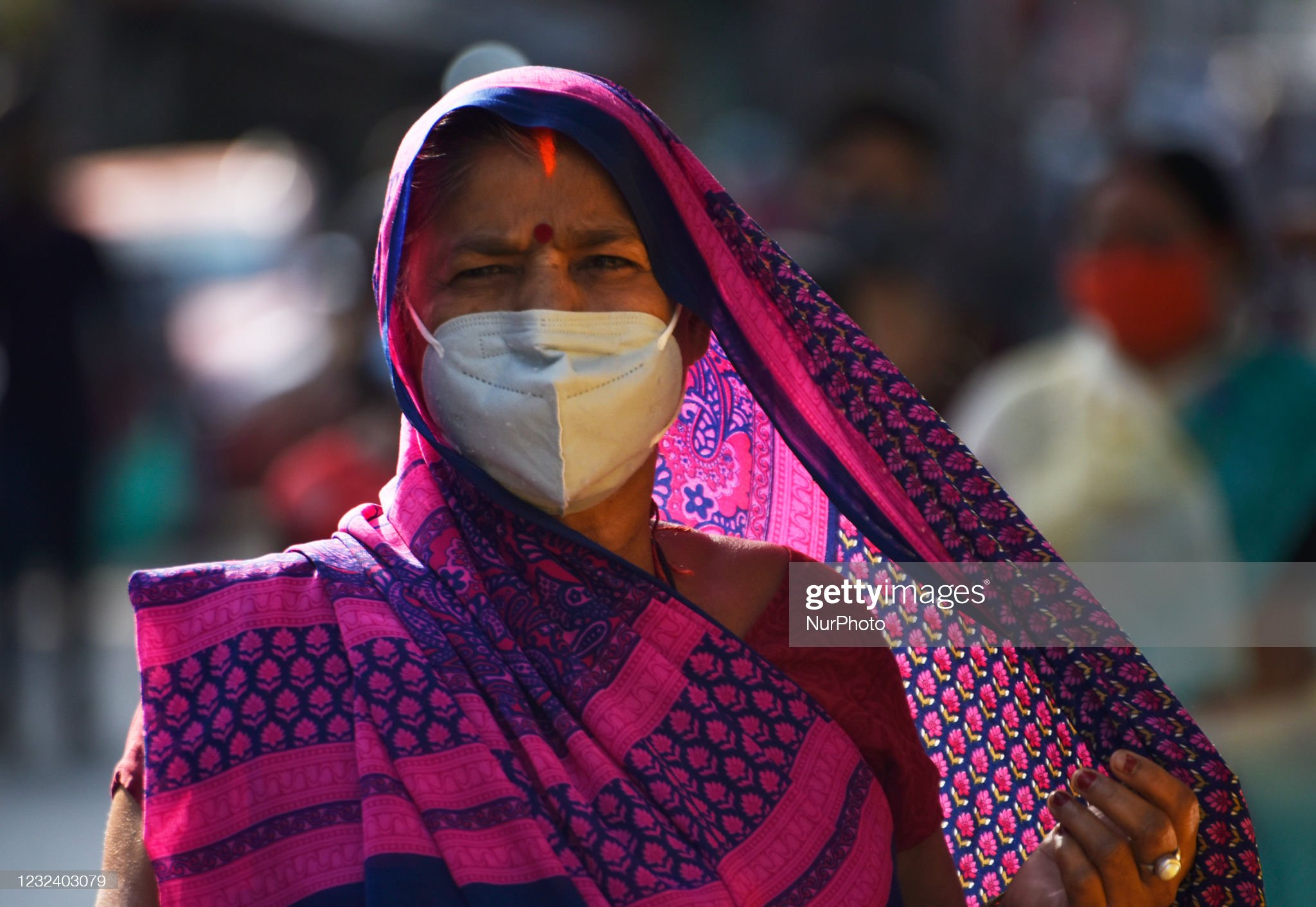 India COVID: Indian woman wearing sari and COVID mask