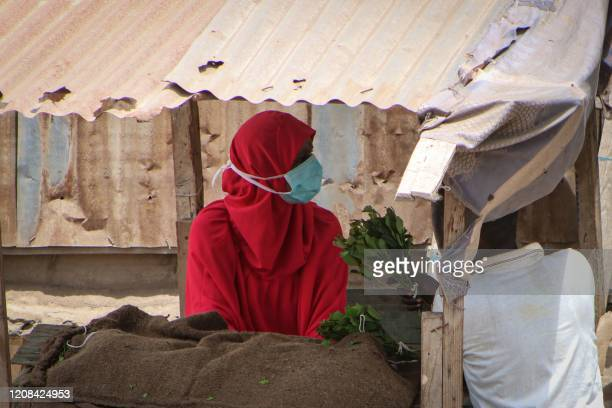 Woman wears a mask and gloves to prevent the spread of the COVID-19 coronavirus as she sells Khat, a leafy mild stimulant known as Miraa, in...