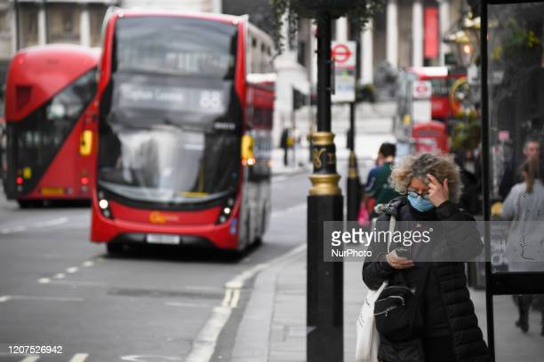 Woman wears a mask as a bus passes on March 17, 2020 in London, England. Boris Johnson held the first of his public daily briefings on the...