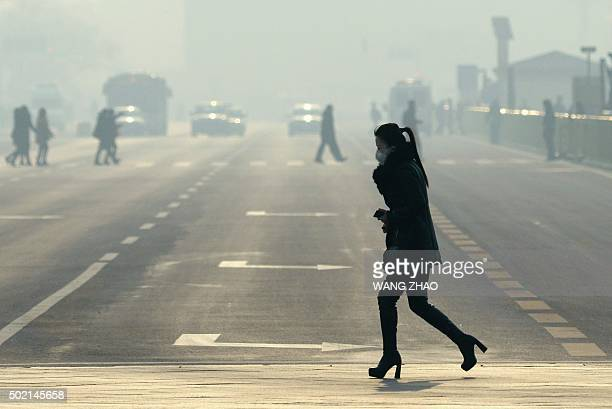 A woman wears a mask as she crosses a street near Tiananmen Square on the third day of a red alert for pollution in Beijing on December 21 2015...