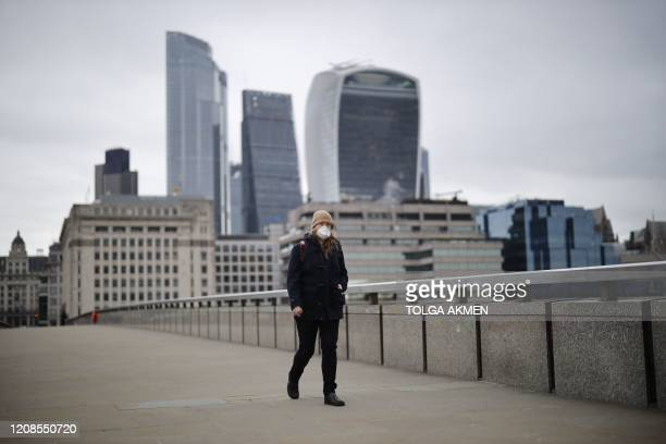 Woman wears a mask as she walks across London Bridge in London on March 30 as life in Britain continues during the nationwide lockdown to combat the...