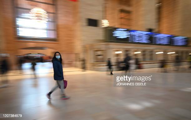 TOPSHOT A woman wears a mask as she walks in Grand Central Terminal in Manhattan on March 16 2020 in New York City Stocks tumbled on March 16 2020...