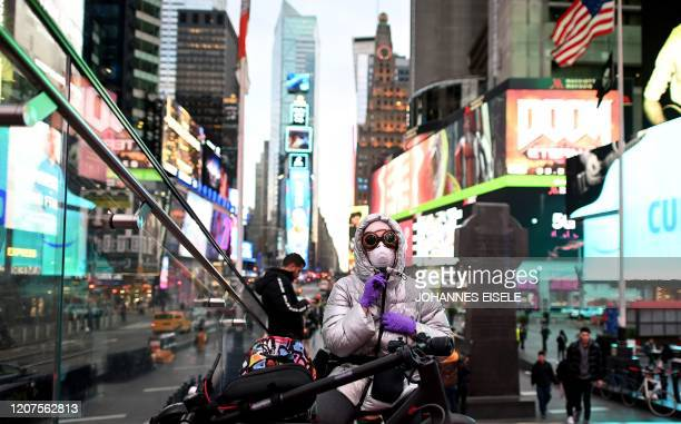 A woman wears a mask in Times Square in Manhattan on March 17 2020 in New York City The coronavirus outbreak has transformed the US virtually...