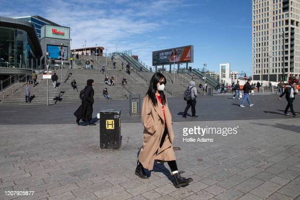 Woman wears a mask near Westfield Stratford City on March 21, 2020 in London, England. Londoners are feeling the impact of shutdowns due to...