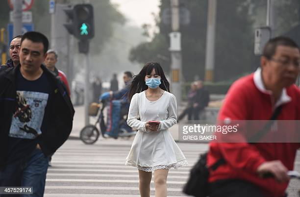 A woman wears a mask on a polluted day in Beijing on October 20 2014 The Chinese capital has been hit by days of thick pollution forcing many...