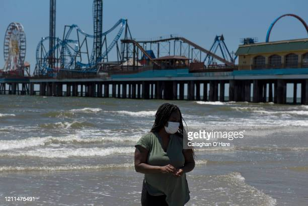 A woman wears a mask on the beach after it was reopened on May 1 2020 in Galveston Texas As part of phase one Gov Greg Abbott reopened the beaches to...
