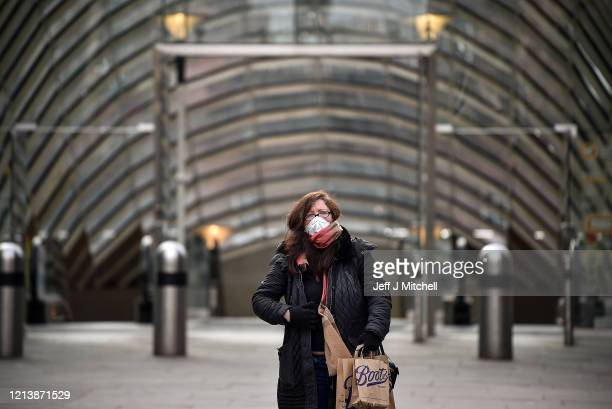 A woman wears a mask outside St Enoch subway station on March 21 2020 in Glasgow Scotland Coronavirus has spread to at least 182 countries claiming...