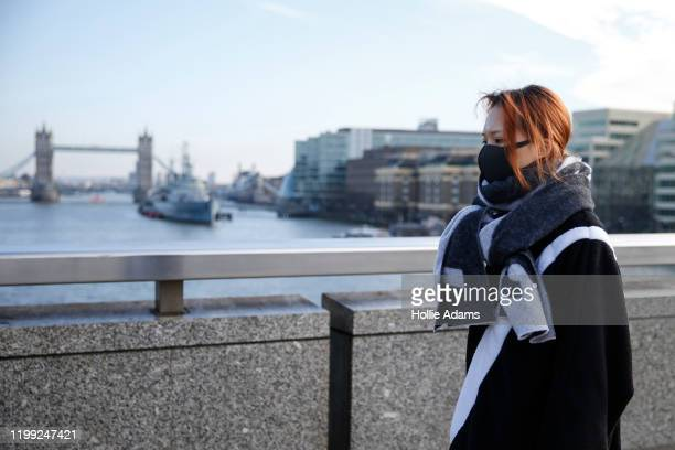 A woman wears a mask while crossing London Bridge on February 7 2020 in London England A British national who reportedly contracted coronavirus while...