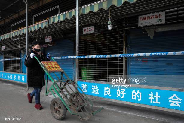 A woman wears a mask while pushing a wheelbarrow past the closed Huanan Seafood Wholesale Market which has been linked to cases of Coronavirus on...