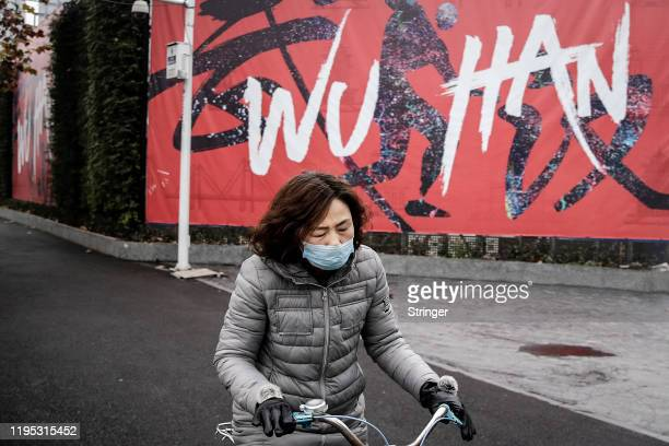 """Woman wears a mask while riding a bicycle on January 22, 2020 in Wuhan, Hubei province, China. A new infectious coronavirus known as """"2019-nCoV"""" was..."""
