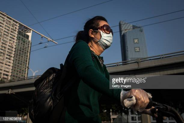 Woman wears a mask while riding a bicycle past the gate of Zhongshan Park on April 28, 2020 in Wuhan, China. Zhongshan Park re-opened to the public...