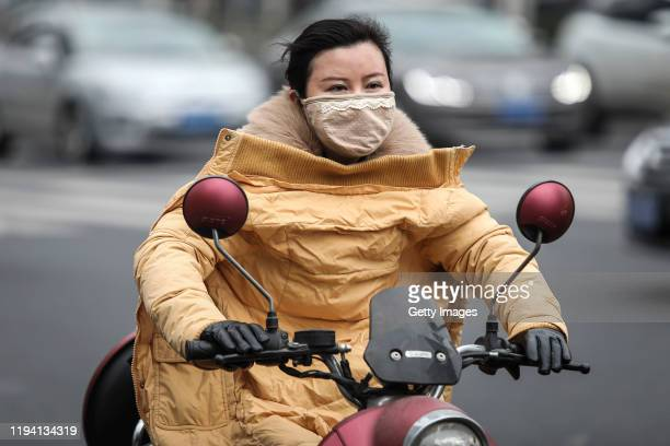 A woman wears a mask while riding an electric bicycle near the closed Huanan Seafood Wholesale Market which has been linked to cases of Coronavirus...
