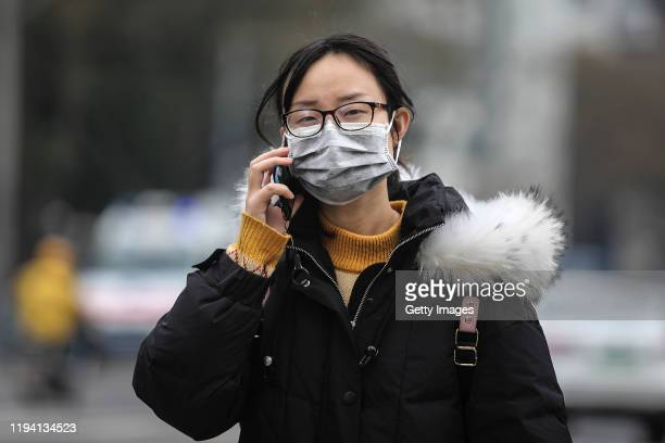A woman wears a mask while walking past the closed Huanan Seafood Wholesale Market which has been linked to cases of Coronavirus on January 17 2020...