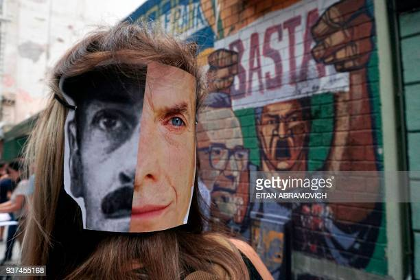 A woman wears a mask with the faces of Argentinian former dictator Jorge Rafael Videla and Argentinian President Mauricio Macri during a march to...