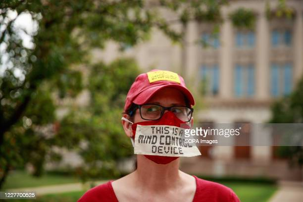 Woman wears a mask written on This is a mind control device during the We Will Not Comply anti mask rally. People protest against both the...