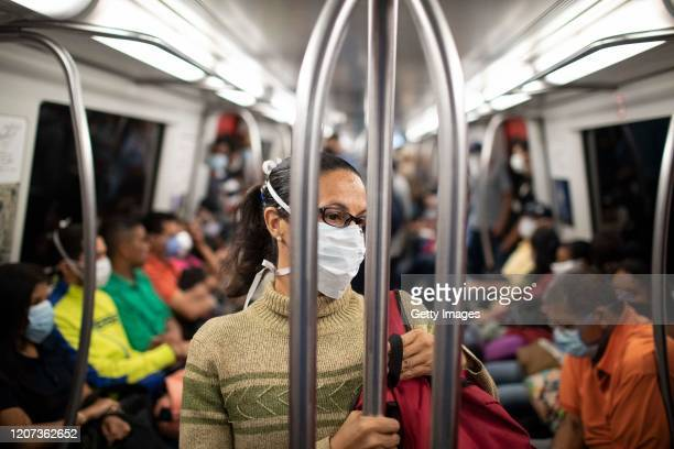 Woman wears a medical mask while traveling in the Caracas Metro on the 1st day of closure of the capital city during the Quarantine in the capital...