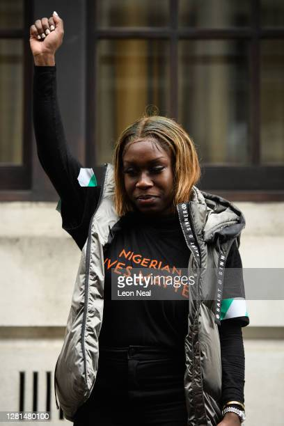 """Woman wears a """"Nigerian Lives Matter"""" shirt as she raises her fist outside the Nigerian Consulate during a demonstration on October 21, 2020 in..."""