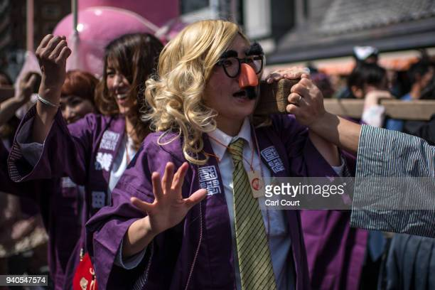 A woman wears a novelty nose and glasses as she helps carry a large pink phallicshaped 'Mikoshi' through the streets during Kanamara Matsuri on April...