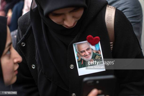 Woman wears a photograph showing the portrait of Iranian Revolutionary Guard Major General Qassem Soleimani during a protest outside the U.S....