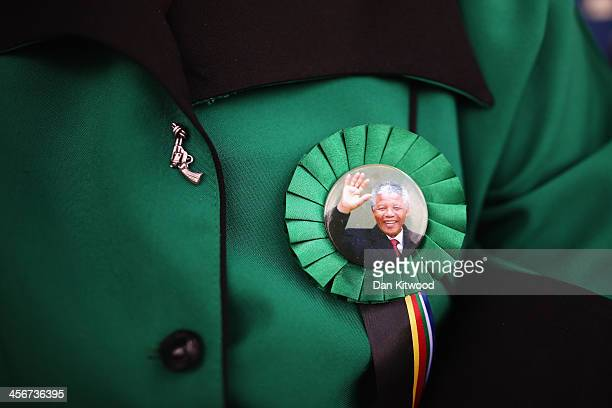 A woman wears a pin badge depicting an image of Nelson Mandela during the funeral service of the former South African President Nelson Mandela during...