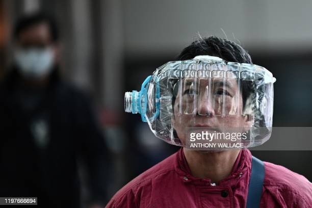 Woman wears a plastic water bottle with a cutout to cover her face, as she walks on a footbridge in Hong Kong on January 31 as a preventative measure...