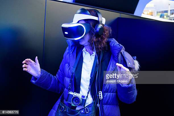 A woman wears a PlayStation VR headset developed by Sony Interactive Entertainment LLC to experience a 360degree game in virtual reality during a...