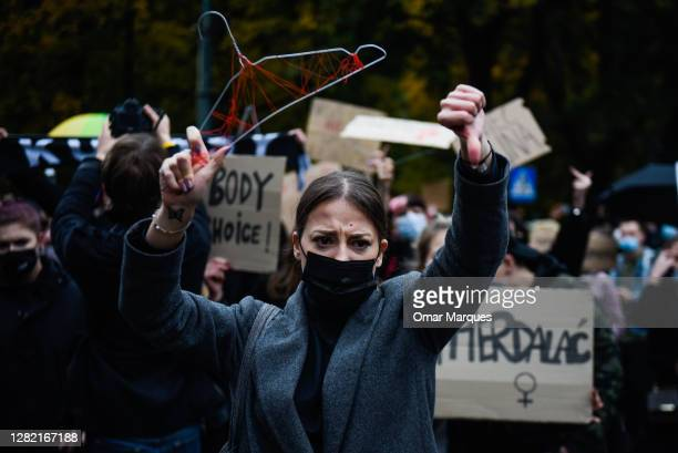 Woman wears a protective face mask and gestures while holding up a coat hanger during the fourth day of protests against the Constitutional Court...