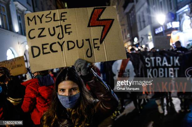 Woman wears a protective face mask and holds a banner as she protest for the third day against the Constitutional Court ruling on tightening the...
