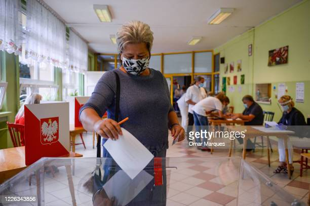 A woman wears a protective face mask as she casts his ballot during Poland's Presidential elections runoff on July 12 2020 in Rybnik Poland The...