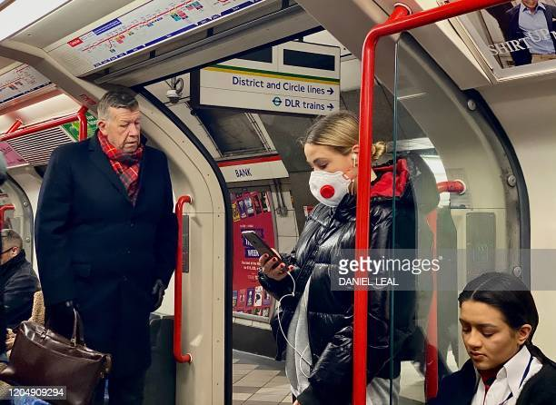A woman wears a protective face mask as she travels on a London tube train carriage at Bank Underground station in central London on March 3 2020 Up...