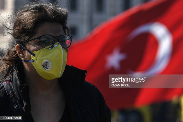 A woman wears a protective face mask as she walks on Galata bridge in Istanbul on March 13 amid the outbreak of COVID19 the new coronavirus Turkey...
