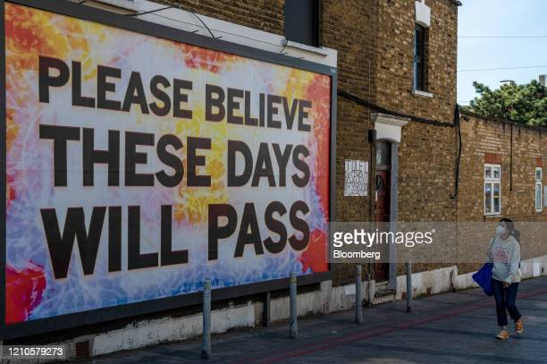 A woman wears a protective face mask as she walks past a basement residential property for let and a billboard relating to the coronavirus pandemic...