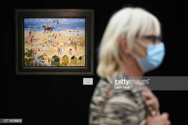 "Woman wears a protective face mask as she walks past ""Low Tide"" by Anna Pugh as she browses the exhibitor's displays at Petworth House, West Sussex..."