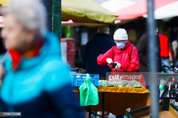 A woman wears a protective face mask due to the spread of coronavirus while doing shopping at the outdoor marketplace in Krakow Poland on April 4th...